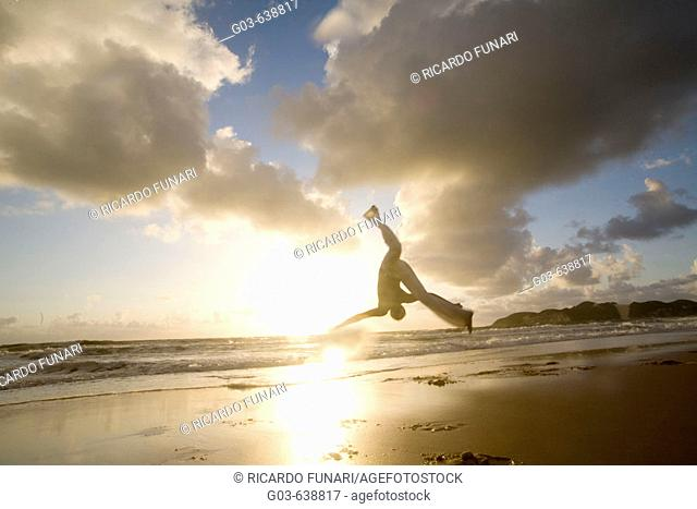 Capoeira player training and exercising in the beach, Brazil