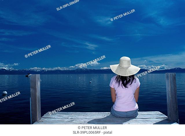 Woman sitting on wooden dock in lake