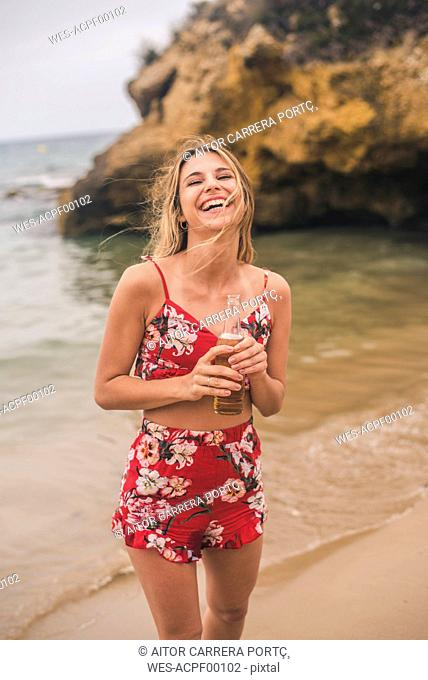 Portrait of happy young woman standing with a beer on the beach