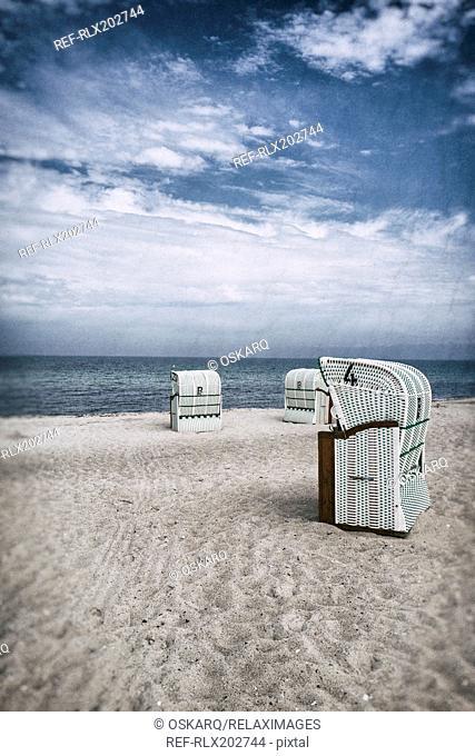 Beach sand seaside hooded beach chairs clouds
