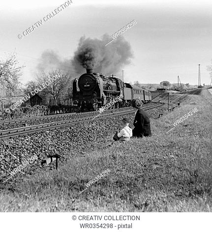two boys looking at a steam engine driving through a field