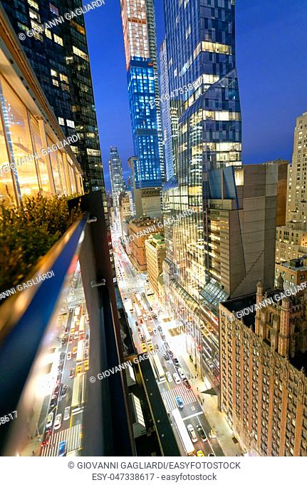 Amazing skyscrapers in Midtown Manhattan, aerial view from rooftop with traffic reflections on the buildings at night
