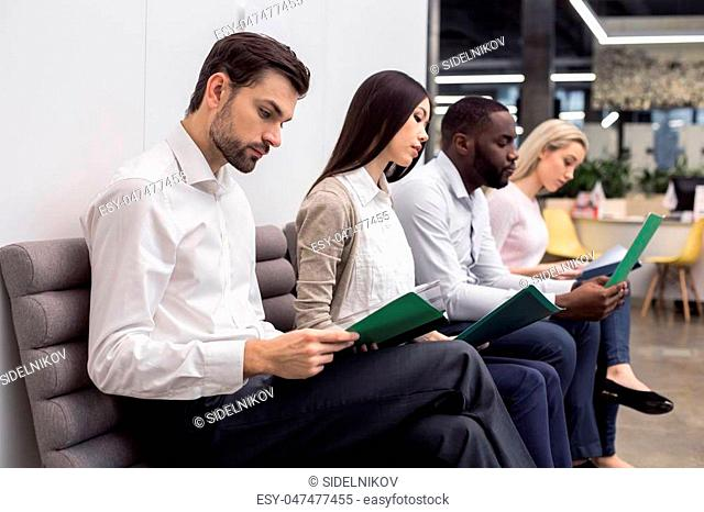 Time for job interview. Young men and women in office. They sitting, holding CVs and waiting for job interview. Nice light interior