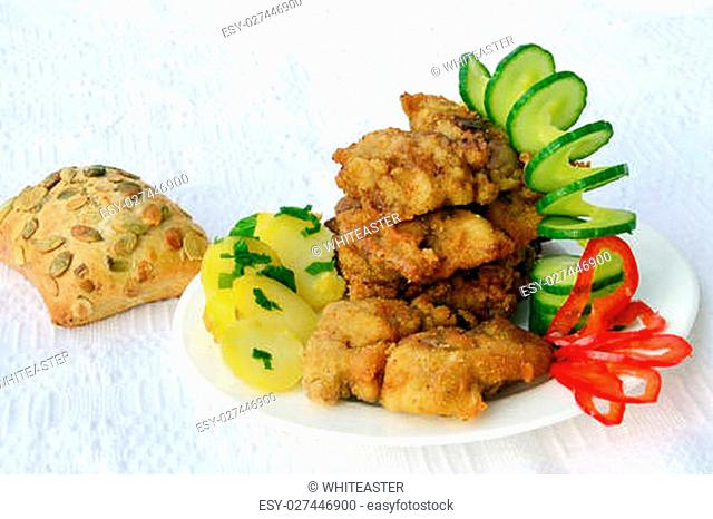 Wiener Schnitzel with potato salad on white table cloth