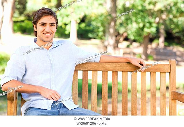 Smiling man sitting on a bench