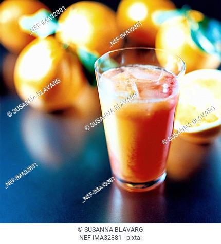 A glass of Campari and orange juice oranges in the background close-up