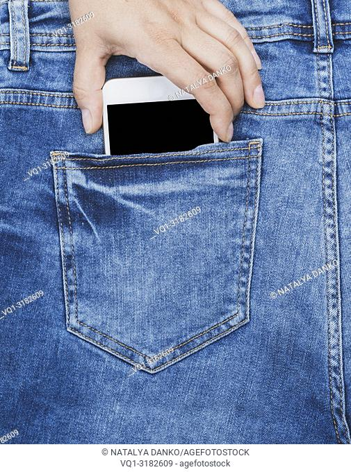 female hand pulls out of the back pocket of a blue jeans smartphone with a blank screen, full frame