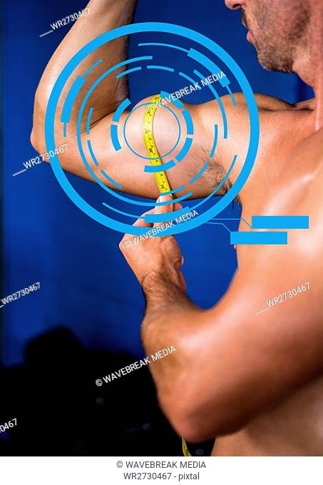 Fit man measuring his biceps at gym with fitness interface