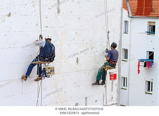 Skilled workers working in a house wall. Getxo, Biscay, Spain, Europe