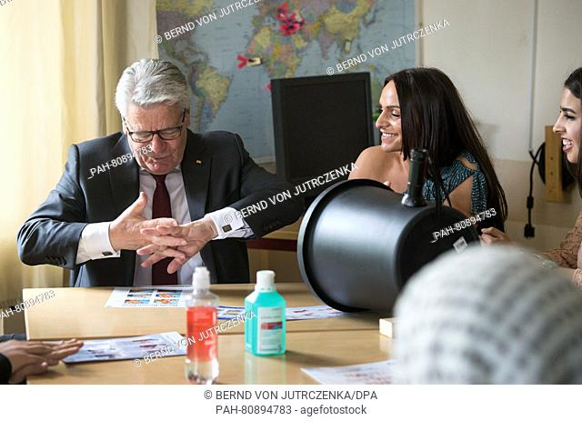 German President Joachim Gauck (L) listens as Belkisa Samardzic (C) and Amal El-Awad (R) explain how to disingect hands at a class for care assitants at the...