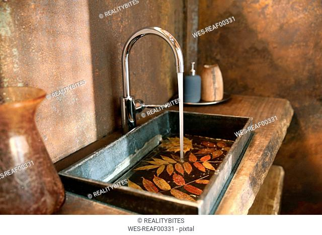 Bathroom sink and stainless steel tap in bathroom with Corten steel wall cladding
