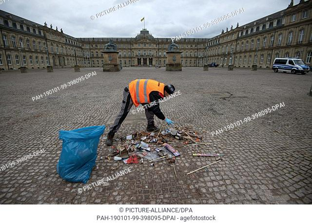 01 January 2019, Baden-Wuerttemberg, Stuttgart: An employee of a cleaning company collects burnt fireworks and other remains of New Year's Eve on the...