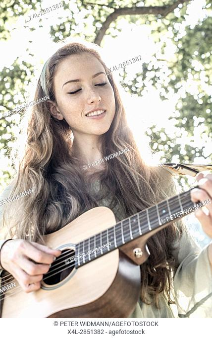 Young singer song-writer musician guitar girl in autumn forest, Vienna, Austria (model-released)