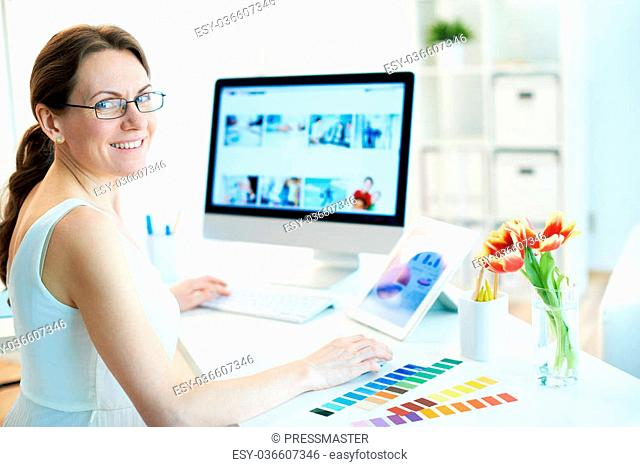 Portrait of happy female designer working and looking at camera