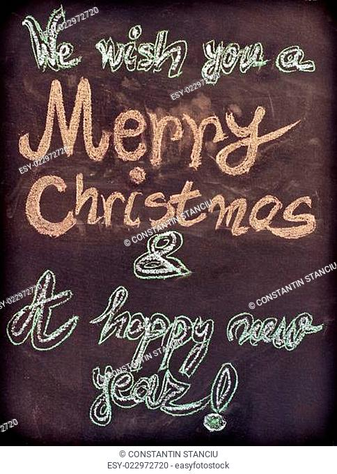 We wish you a Merry Christmas and a happy new year, hand writing with chalk on blackboard, vintage concept