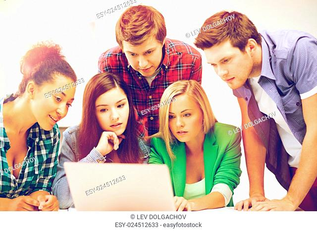 education and internet concept - group of international students looking at laptop at school