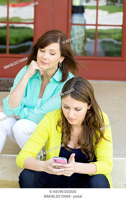 Caucasian mother watching daughter use cell phone