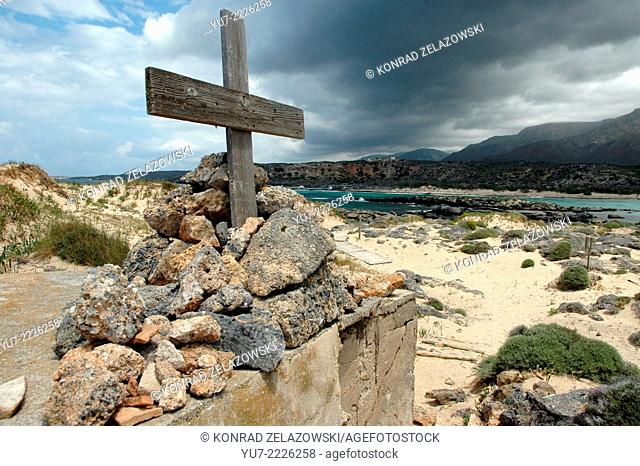 Wooden cross with heavy, dark, rainy clouds above on small island Elafonissi near southeast tip of greek island of Crete