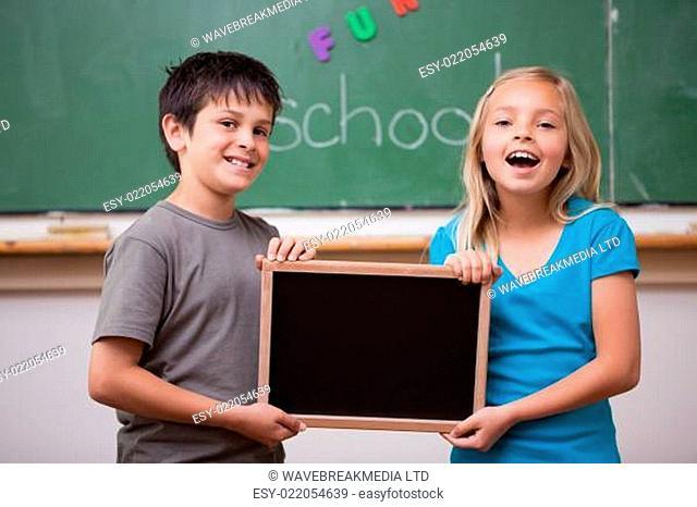 Happy pupils holding a school slate