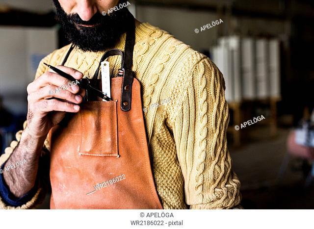 Midsection of carpenter keeping pencil in apron pocket at workshop