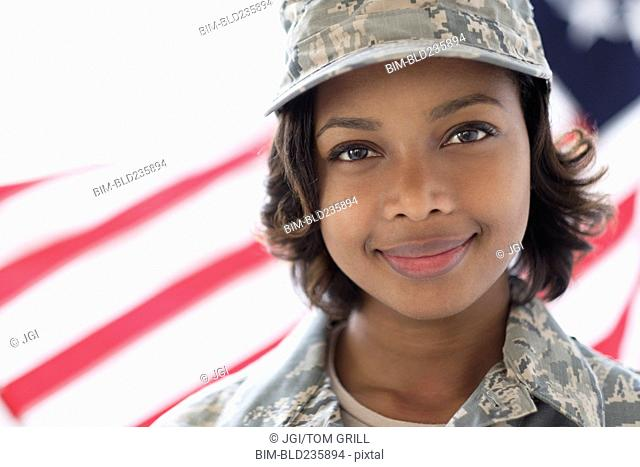 Portrait of smiling Mixed Race soldier near American flag