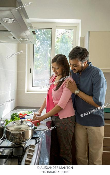 man standing behind woman in kitchen while she cooks