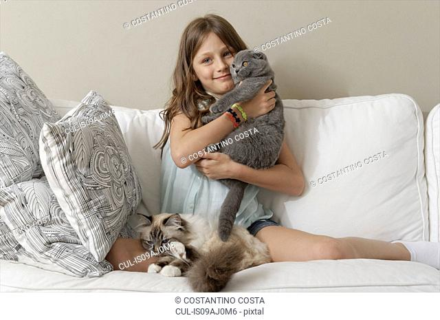 Girl with two cats on sitting room sofa