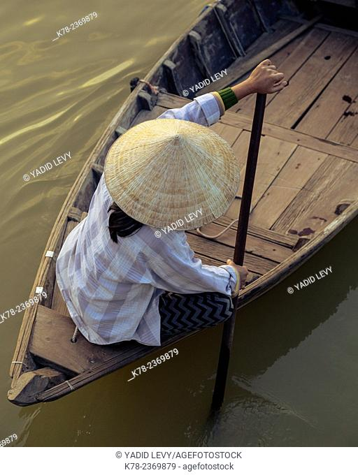 Woman rowing a boat at the Thu Bon river, Hoi An, Vietnam