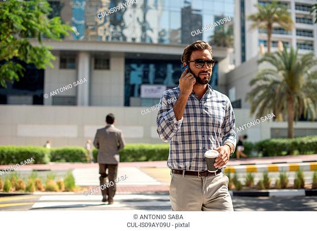 Young man on pedestrian crossing talking on smartphone, Dubai, United Arab Emirates