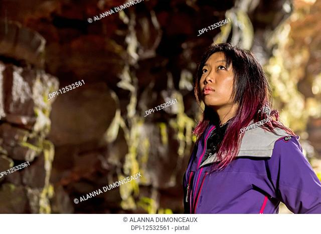 A side profile close-up of an asian female hiker looking upwards at the cave walls in a lava tube cave; Iceland