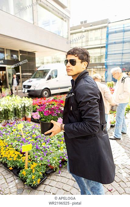 Man looking away while holding flower pot in market