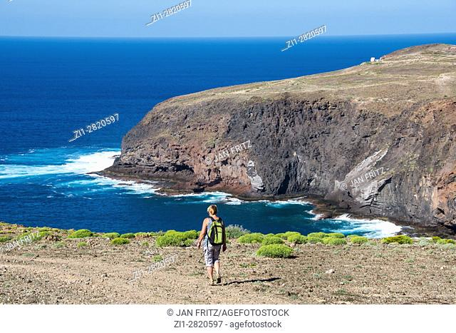 woman walking alongside cliff coast at gran canaria, spain