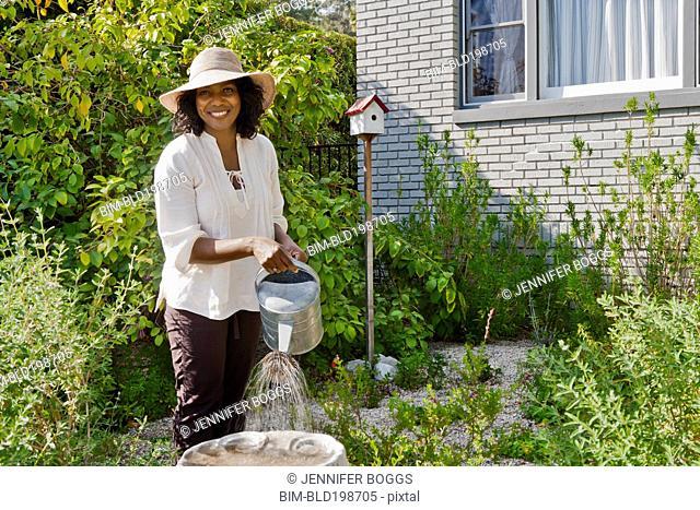 Smiling woman watering plants in garden