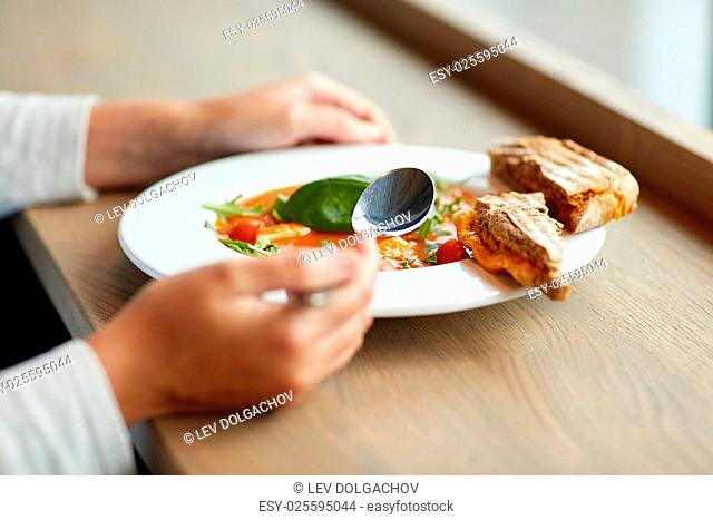 food, dinner, culinary and people concept - woman eating gazpacho soup with bread and spoon at restaurant