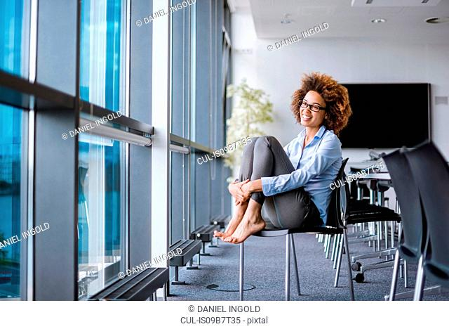 Happy barefoot young businesswoman sitting on office chair