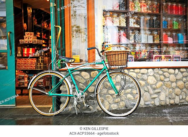 Cruiser bicycle with basket parked outside a Candy Store during a snowfall. Banff, Alberta, Canada