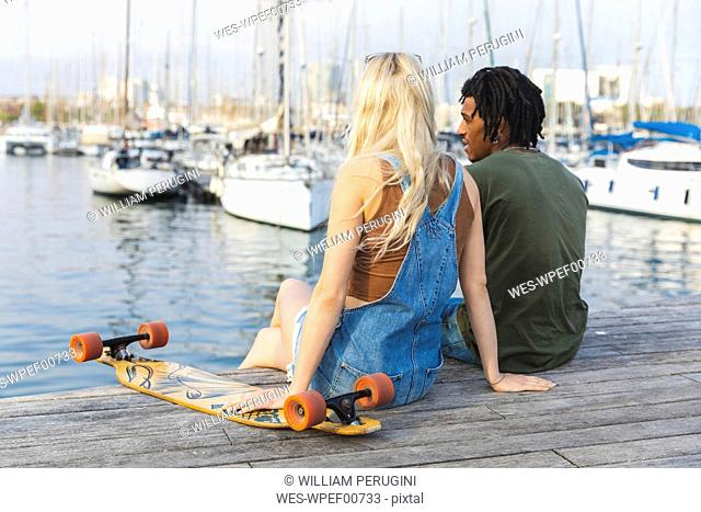 Spain, Barcelona, multicultural young couple with longboard relaxing at harbour