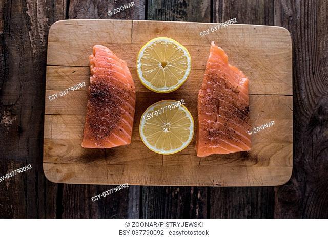 raw salomon on chopping board with lemon