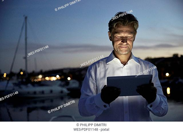 Portrait of smiling mature man standing in front of harbour at evening twilight looking at tablet