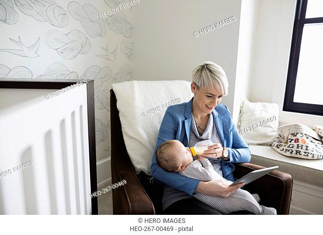 Mother with digital tablet feeding baby son bottle