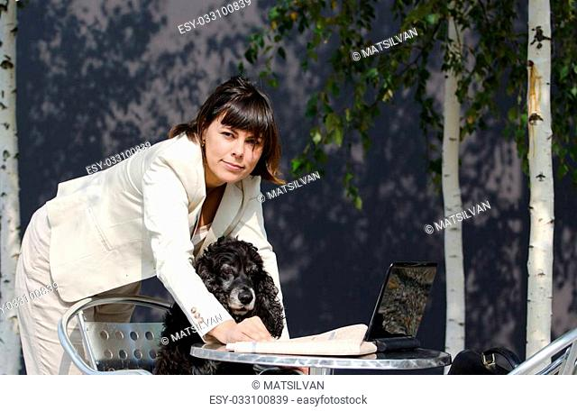 Business woman standing up with her personal computer and showing her dog the stock market in a financial newspaper