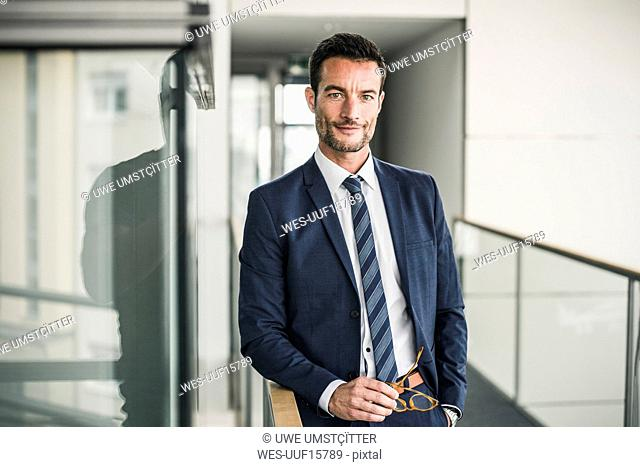 Portrait of a successful businessman, standing in office building