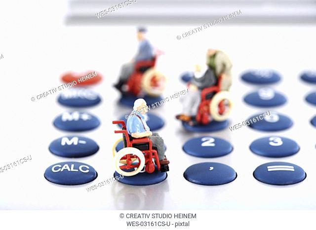 Figurine on wheelchairs on calculator