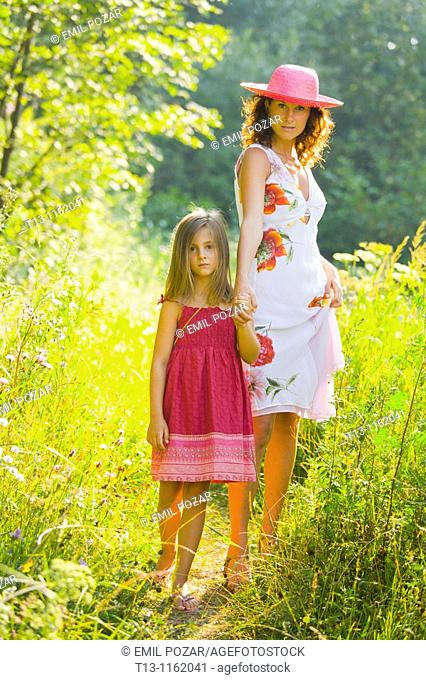 Mother and daughter are walking in the woods