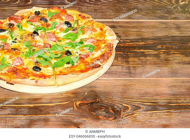Fragment of the cooked round pizza with sausages, mushrooms, olives and arugula on the old wooden table