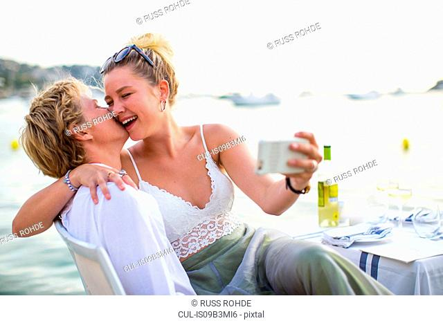 Young couple laughing and taking selfie at waterfront restaurant, Majorca, Spain