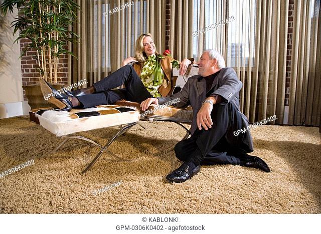 Portrait of romantic mature couple sitting in modern downtown loft