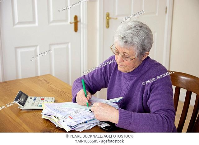 Britain, UK, Europe  Senior woman pensioner with a big pile of bills on the table writing a cheque to pay