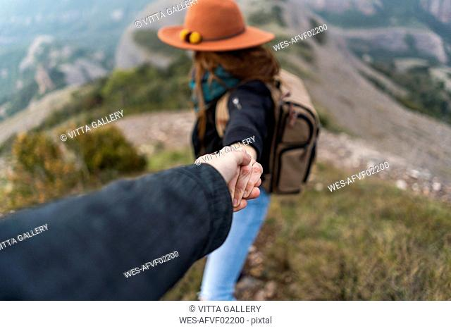 Woman with hat, standing on mountain, holding on to man's hand