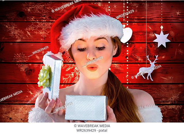 Woman in santa hat looking at christmas gift